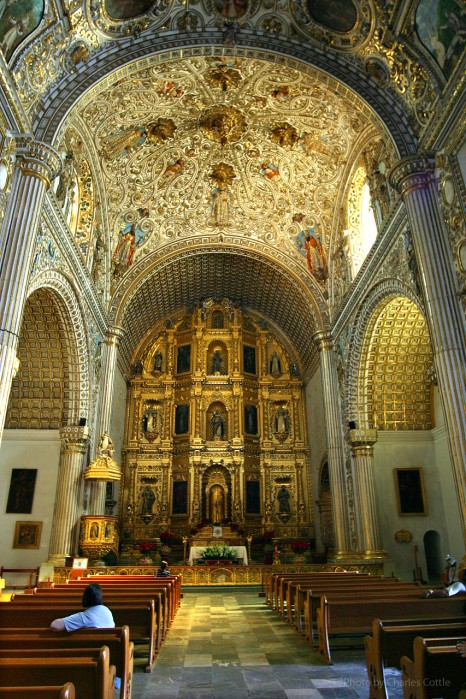 Ornately decorated vaulted ceilings and golden altar of church interior