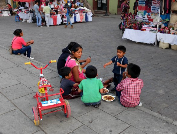 Indigenous vendor feed her children what appears to be pozole.