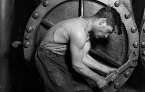 Lewis Hine photo of muscular worker tightening bolts.