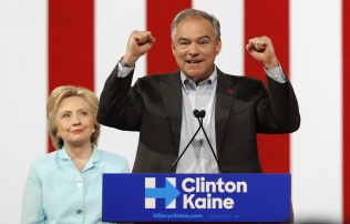 Democratic U.S. presidential candidate Clinton listens to her running-mate Democratic U.S. vice presidential candidate Kaine after she introduced him during a campaign rally in Miami