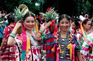 Two young women participants, each dressed in colorful dresses and carrying pineapples on their shoulders.