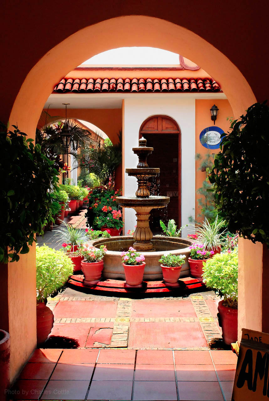 Small three tiered fountain seen through an archway onto a patio.