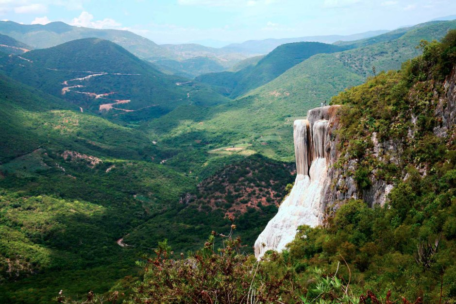Long view of what appears to be a waterfall in mountainous terrain.